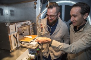Kyle Nel, executive director, Lowe's Innovation Labs, left, and Jason Dunn, CTO and co-founder, Made in Space, examine a 3D printer in a mock-up of the International Space Station (ISS) in New York on Wednesday, October 28, 2015. Lowe's Innovation Labs, the disruptive innovation hub of Lowe's Companies, Inc., has partnered with aerospace company Made in Space, to become the first to launch a commercial 3D printer to space. The printer, the first permanent additive manufacturing facility for the ISS, will bring tools and technology to astronauts in space.(Jim Sulley/Newscast Creative)