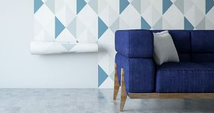 A blue sofa in front of geometric wallpaper being applied