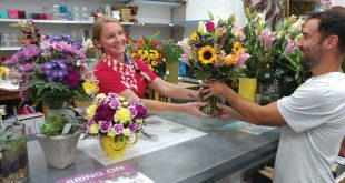 Woman at floral shop serving a customer