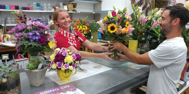 Woman at floral shop serving a customer