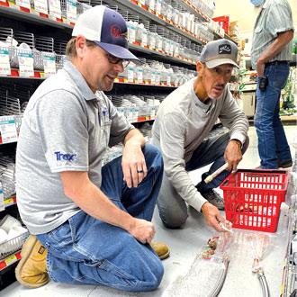 Hardware store employee helping customers with plumbing supplies