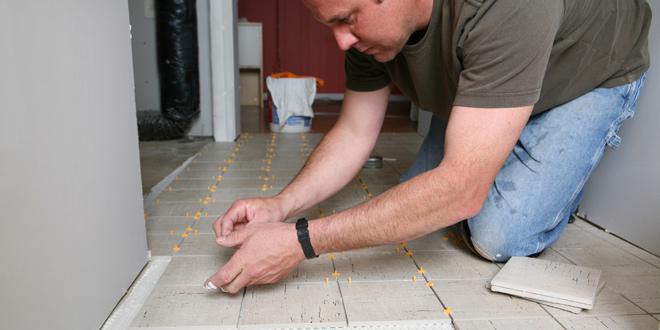 Man installing a tile floor