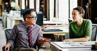Man mentoring a woman in an office